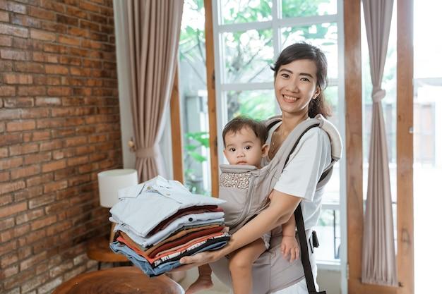 自宅で服にアイロンをかける若い女性の笑顔