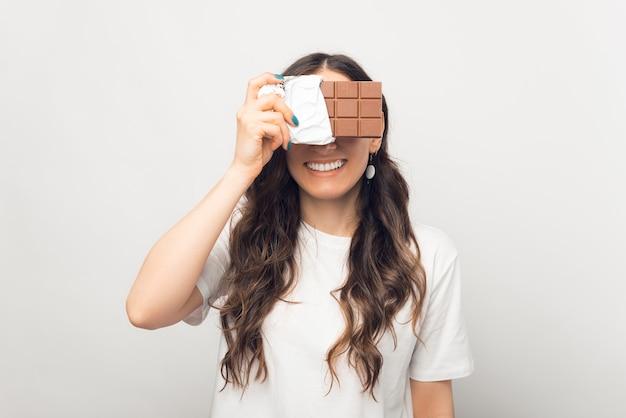 Улыбающаяся молодая женщина закрывает глаза и лицо плиткой шоколада.