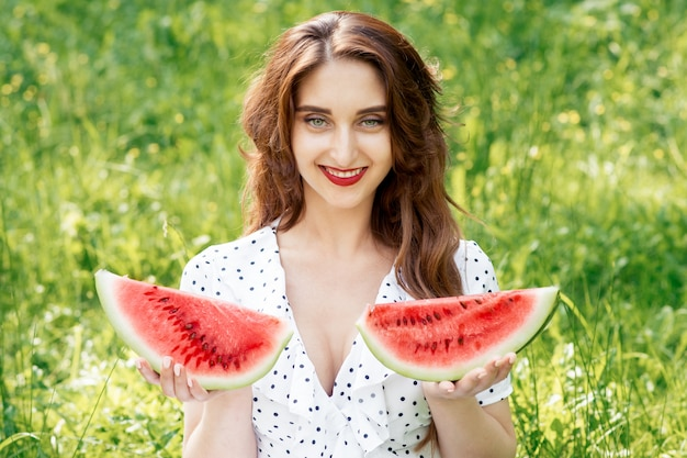 Smiling young woman is holding two slices of watermelon.