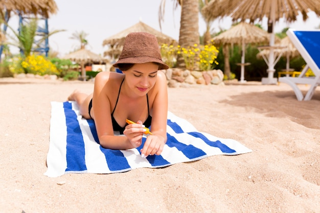 Smiling young woman is lying on striped towel on the sand at the beach and applying sun cream on her hand.