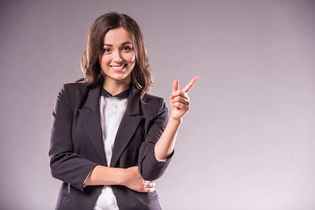 Smiling young woman is pointing at copyspace.