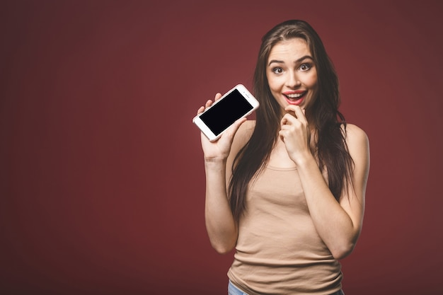 Smiling young woman is pointing on smartphone standing on red background.