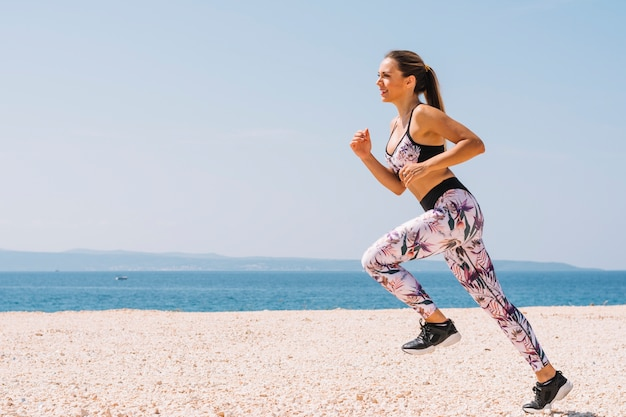 Smiling young woman jogging near the beach against blue sky