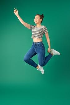 緑の上を空中でジャンプする笑顔の若い女性。