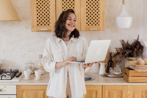 A smiling young woman in a kitchen enjoying a video conversation getting acquainted on a website a woman spends time on a social network