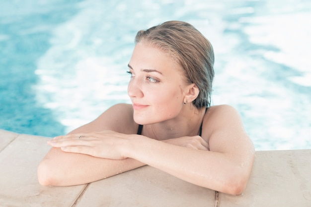 Smiling young woman leaning on the swimming pool edge
