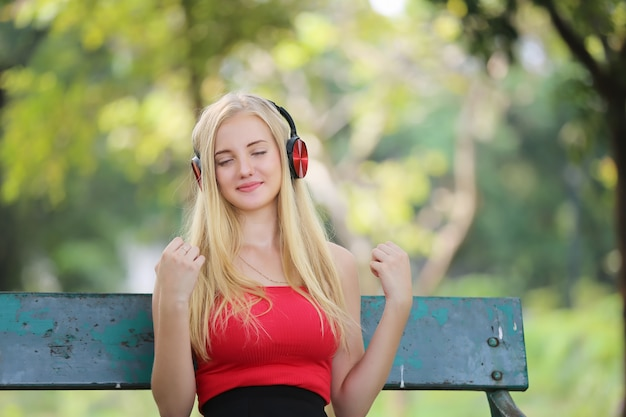 Smiling young woman listening music over headphones in park