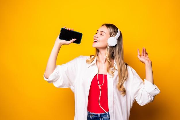 Улыбающаяся молодая женщина, слушающая музыку в наушниках и использующая смартфон, изолирована над желтой стеной