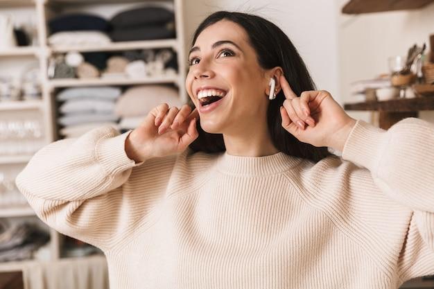 Улыбающаяся молодая женщина слушает музыку в наушниках, стоя на кухне