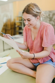 워크숍에서 캔버스 종이보고 웃는 젊은 여자