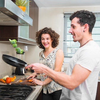 Smiling young woman looking at her husband throwing broccoli in frying pan