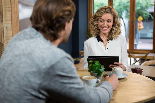 コーヒーショップのテーブルで男を見て笑顔の若い女性