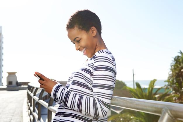 携帯電話でテキストを見て笑顔の若い女性