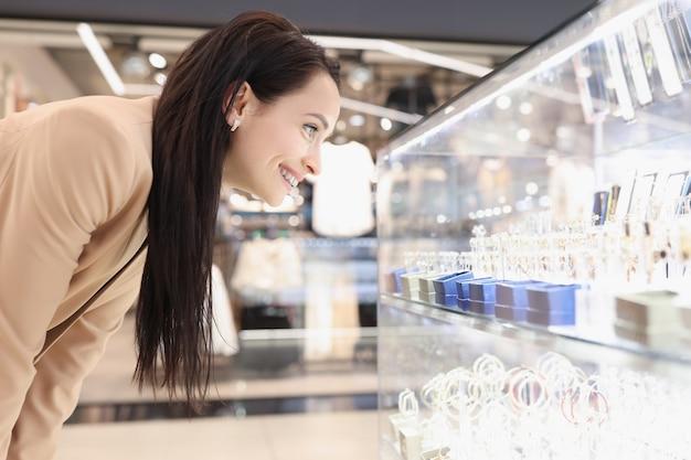 笑顔の若い女性がジュエリーでショーケースを見て
