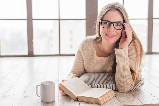 La giovane donna sorridente che si trova sul pavimento di legno duro con consegna gli occhiali che tengono il libro