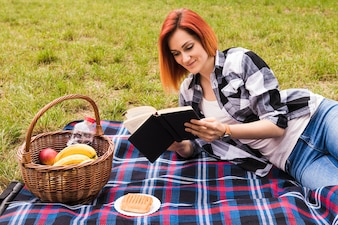 Smiling young woman lying on blanket reading book at picnic