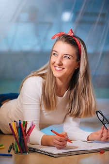 Улыбающаяся молодая женщина, лежа на полу и рисующая цветными маркерами