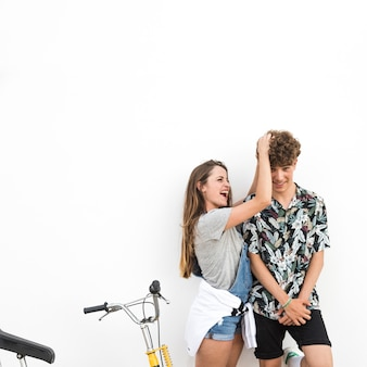 Smiling young woman making fun with her boyfriend standing with bicycle against white backdrop