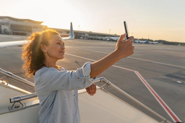 空港でスマートフォンで自分撮りを作る笑顔の若い女性