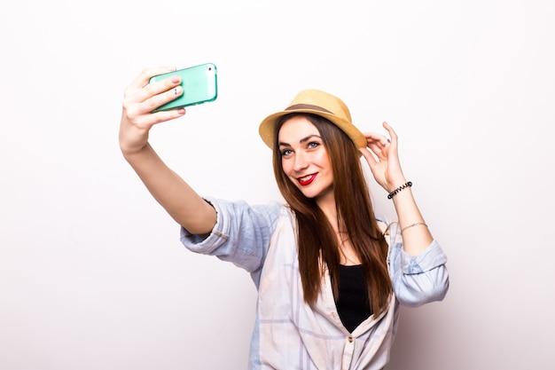 灰色の上にスマートフォンでselfie写真を作る笑顔の若い女性