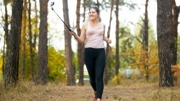 森の中を走りながらスマートフォンで自分撮り写真を作る笑顔の若い女性。
