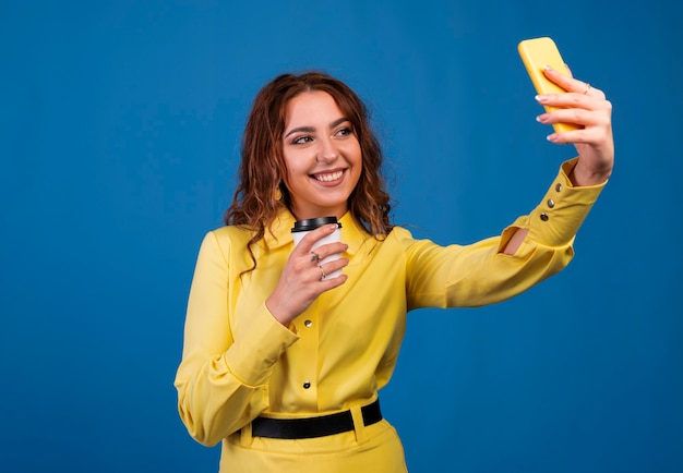 Smiling young woman making selfie photo on smartphone over blue background.