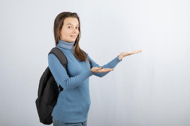 Улыбается модель молодой женщины с рюкзаком, показывая руки.