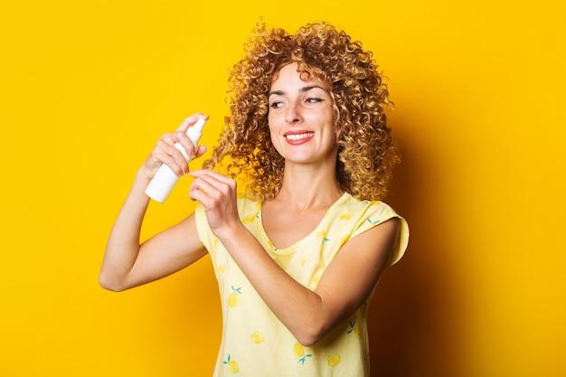 웃는 젊은 여자는 노란색 배경에 스프레이로 그녀의 머리카락을 보습합니다. 헤어 케어.