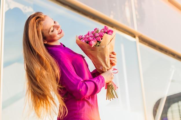 花とモダンなガラスのオフィスのインテリアの近くで若い女性の笑顔