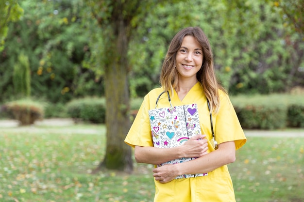 彼女の手にハートのフォルダーを持つ笑顔の若い女性看護師