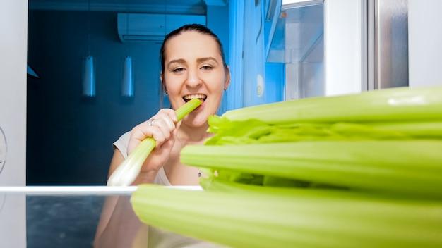 夜のキッチンでセロリを食べるダイエット中の若い女性の笑顔。ダイエットと健康的な栄養の概念。