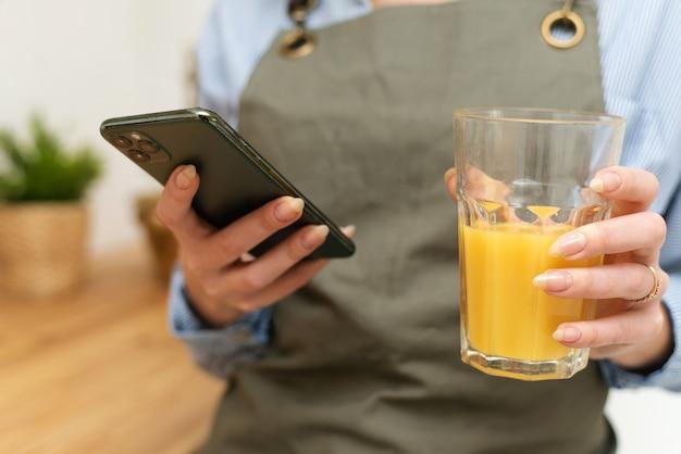 Улыбается молодая женщина по телефону, стоя на кухне, пьет сок. закройте вверх.
