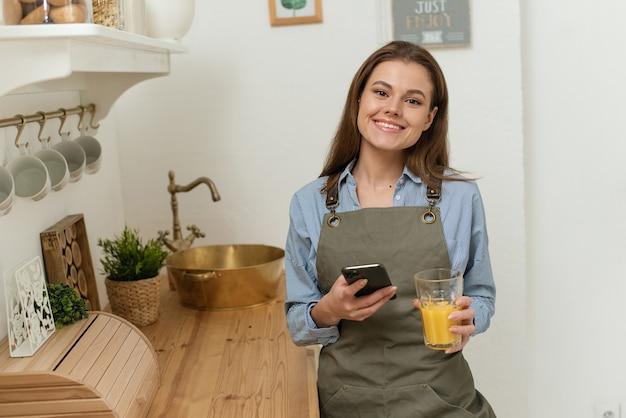 Улыбается молодая женщина по телефону, стоя на кухне, пьет сок портрет веселых молодых.