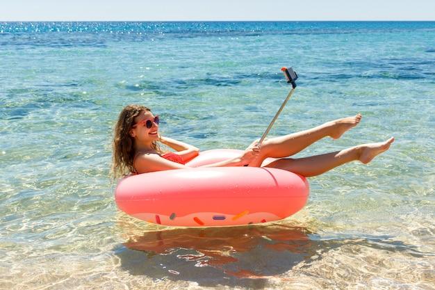 웃는 젊은 여자 또는 십대 소녀 해변에서 스마트 폰으로 풍선 도넛에 셀카를 만든다