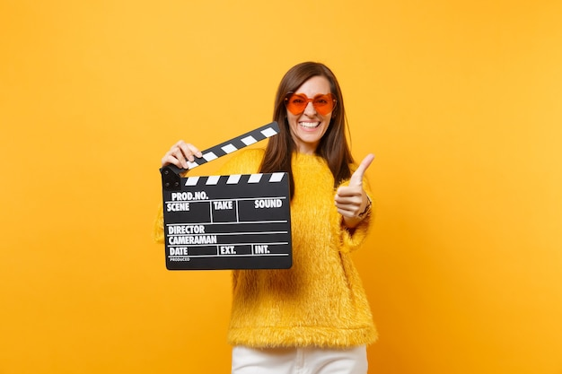 Smiling young woman in orange heart eyeglasses showing thumb up, holding classic black film making clapperboard isolated on yellow background. people sincere emotions, lifestyle. advertising area.