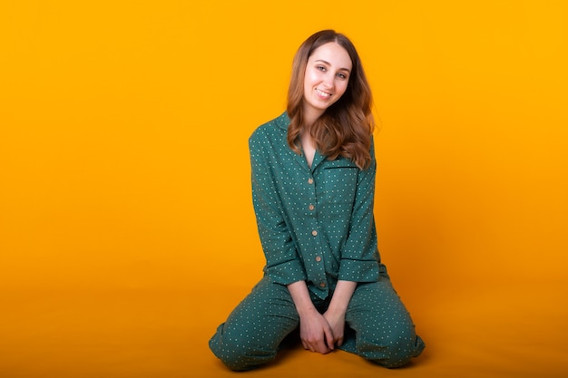 Smiling young woman in pajamas home wear posing while resting at home isolated on yellow wall