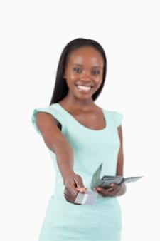 Улыбается молодая женщина с ее кредитной карты