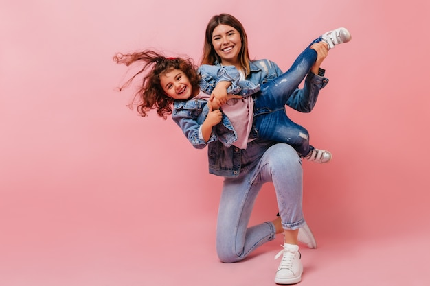 Smiling young woman playing with daughter. studio shot of happy mom and preteen kid in denim attire.