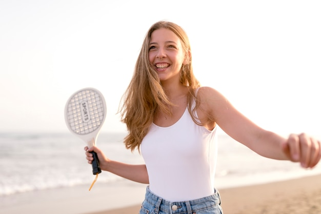Smiling young woman playing with racket at beach