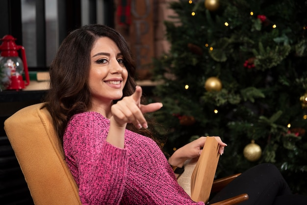 Sorridente giovane donna puntare il dito contro la fotocamera.