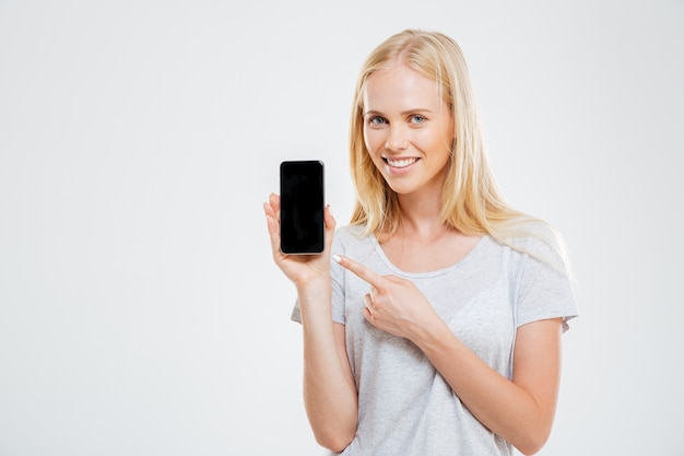 Smiling young woman pointing finger at blank smartphone screen isolated on a white wall