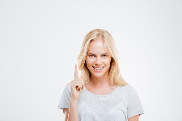 Улыбающаяся молодая женщина, указывая пальцем вверх над белой стеной
