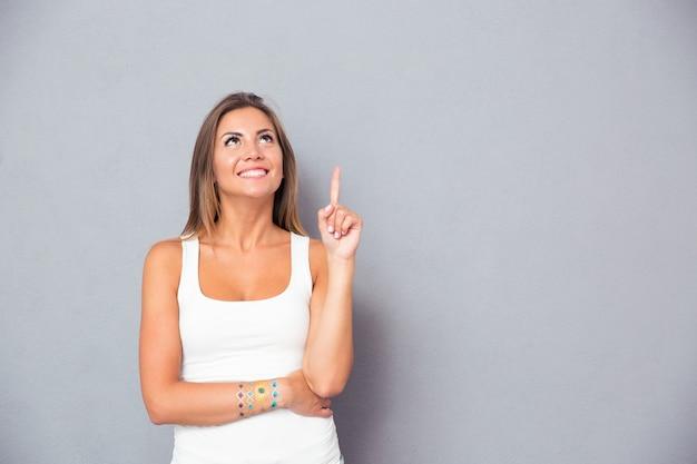 Улыбающаяся молодая женщина, указывая пальцем вверх
