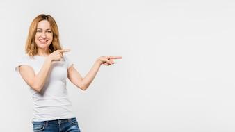 白い背景で隔離の指を指している若い女性の笑みを浮かべてください。