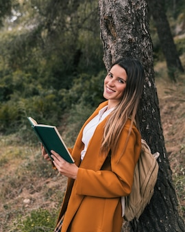 Smiling young woman posing under the tree with book in her hand