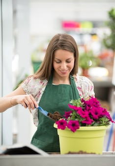 Smiling young woman potting surfinia or petunias