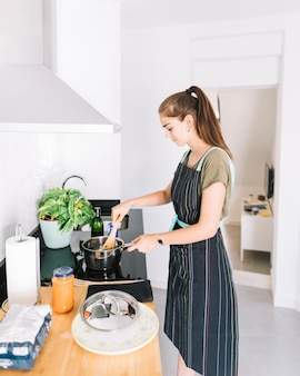 전기 스토브에 소스 팬에서 음식을 준비하는 젊은 여자를 웃 고