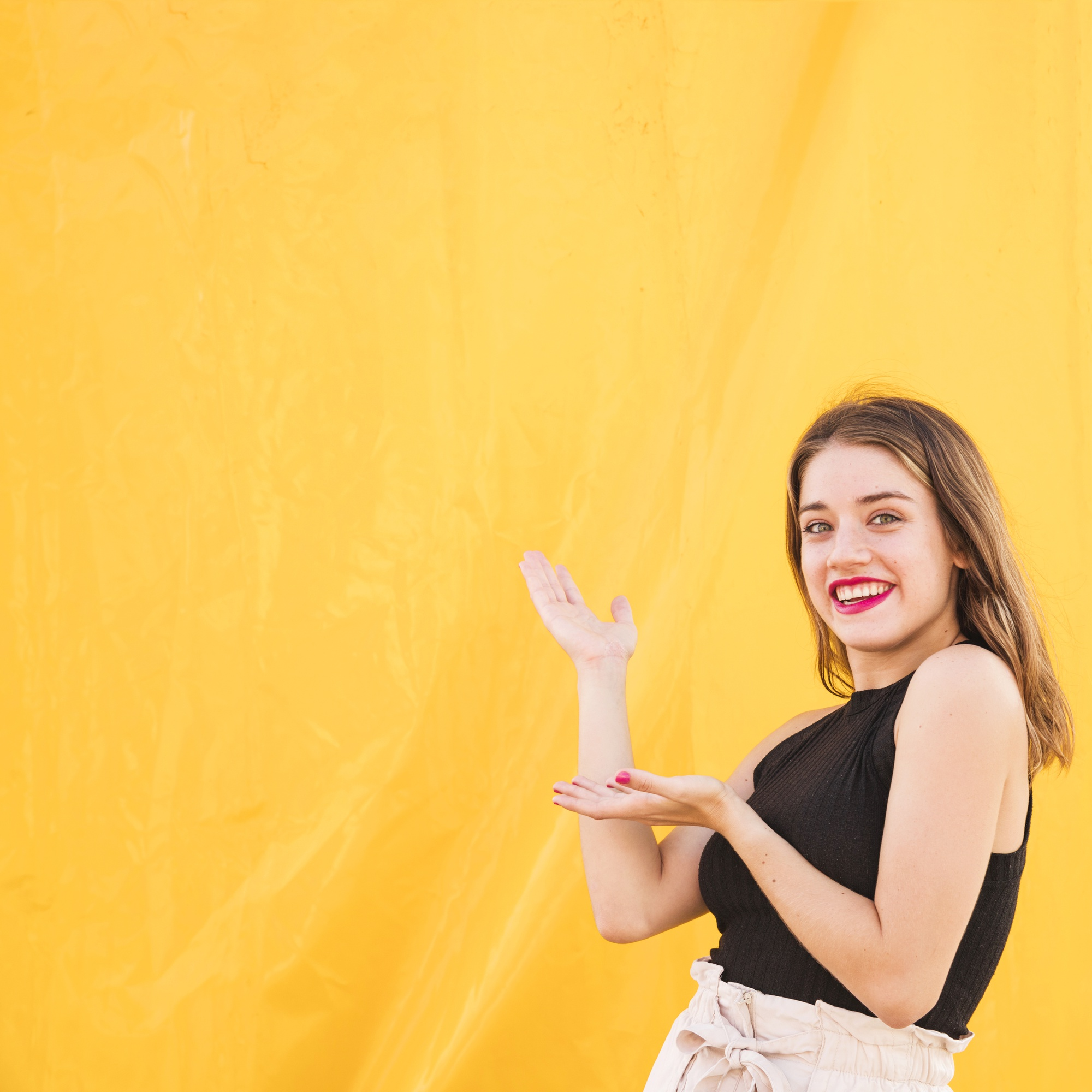 Smiling young woman presenting on yellow background