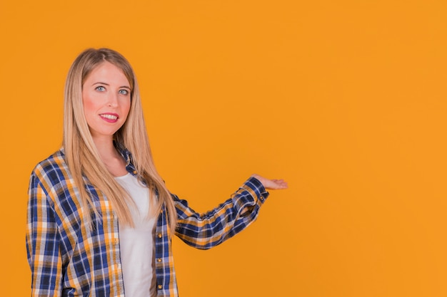 Smiling a young woman presenting something against an orange backdrop