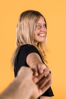 Smiling young woman pulling her boyfriend against yellow wall